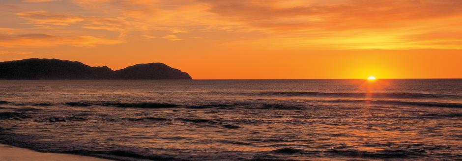 sunrise at wainui-beach with caravan for hire
